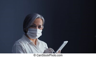 Mature gray hair doctor in protective mask signing on tablet...