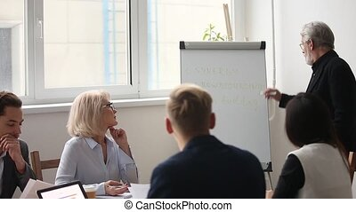 Mature grey haired business coach giving presentation to...