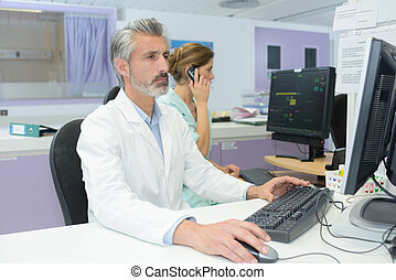 mature handsome doctor looking at exam results on the computer
