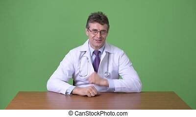Mature handsome man doctor against green background