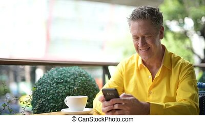 Mature Handsome Man Sitting In Coffee Shop While Using...