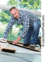 mature handyman installing wooden floor in building