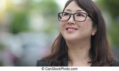 Mature happy beautiful Asian businesswoman thinking in the streets outdoors