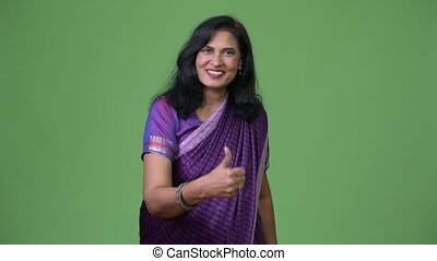 Mature happy beautiful Indian woman giving thumbs up while...