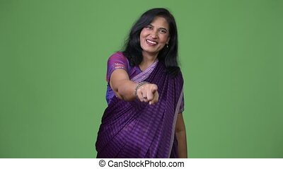 Mature happy beautiful Indian woman pointing at camera while...