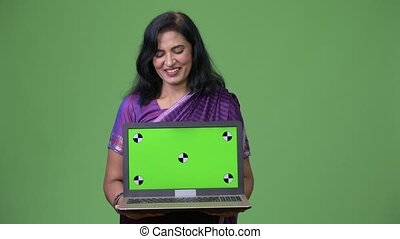 Mature happy beautiful Indian woman showing laptop - Studio...