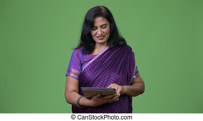 Mature happy beautiful Indian woman smiling while using...