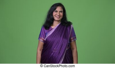 Mature happy beautiful Indian woman smiling while wearing...
