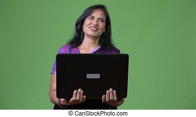 Mature happy beautiful Indian woman thinking while laptop -...