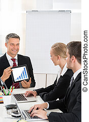 Businessman Discussing Graph To Colleagues