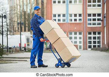 Deliveryman Holding Trolley Loaded With Cardboard Boxes