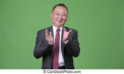 Mature happy Japanese businessman clapping hands