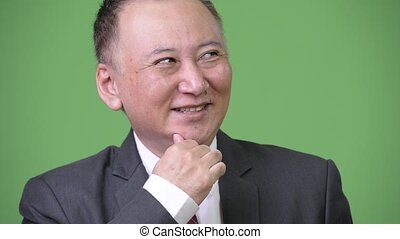 Mature happy Japanese businessman smiling while thinking