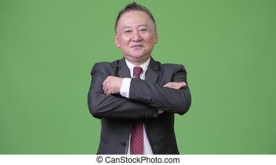 Mature happy Japanese businessman smiling with arms crossed
