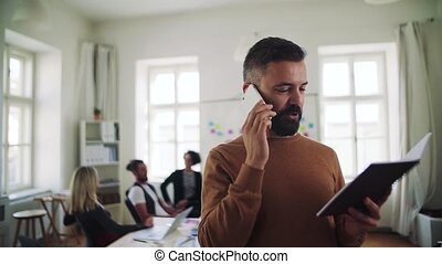 Mature hipster businessman with smartphone working in a...