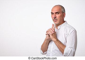 Mature hispanic man acts like spy or policeman