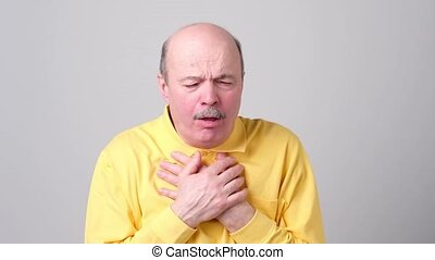 Mature hispanic man in yellow t-shirt man coughing being...