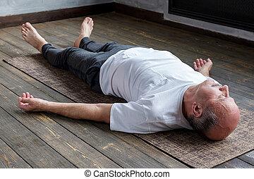 Mature hispanic man in yoga corpse pose in wooden floor.