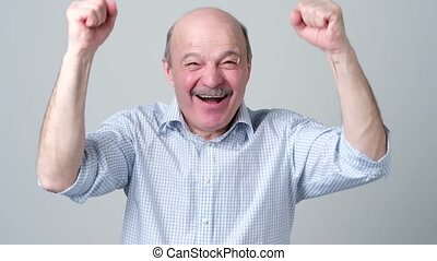 Mature hispanic man is happy with his win. He is holding his...