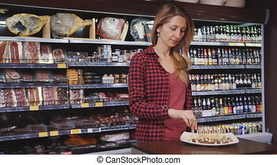 Mature housewife standing in hypermarket and tasting fresh...