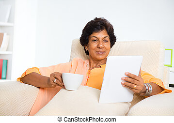 Mature Indian woman using computer tablet