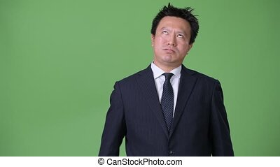 Mature Japanese businessman against green background -...