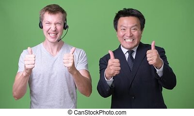 Mature Japanese businessman and young Scandinavian man worker together