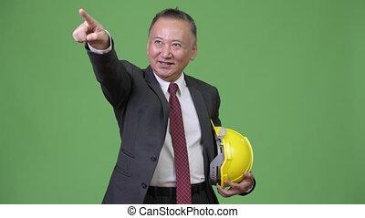 Mature Japanese businessman as engineer directing - Studio...