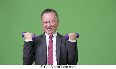 Mature Japanese businessman exercising - Studio shot of...