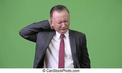 Mature Japanese businessman having neck pain