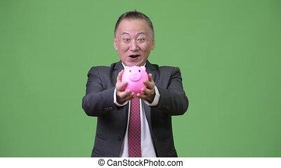 Mature Japanese businessman holding piggy bank