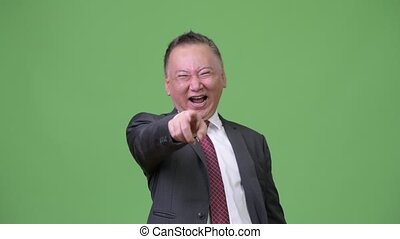 Mature Japanese businessman laughing out loud - Studio shot...