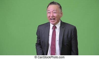Mature Japanese businessman laughing out loud - Studio shot...