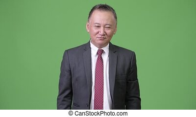 Mature Japanese businessman nodding yes - Studio shot of...