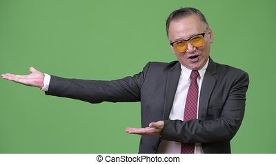 Mature Japanese businessman wearing sunglasses against green...