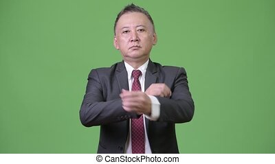Mature Japanese businessman with arms crossed