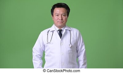 Mature Japanese man doctor against green background