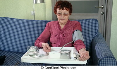Mature lady examining her health state with manometer