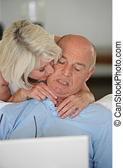 mature lady kissing her husband browsing with laptop