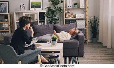 Mature lady talking to psychologist lying on sofa in office...