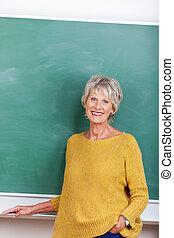 Mature lady teacher - Attractive mature teacher standing in...