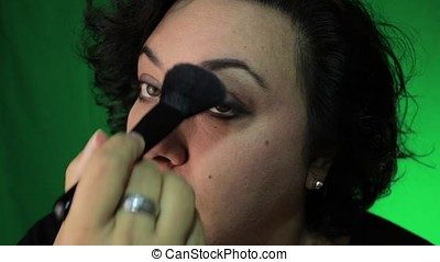mature latina woman brushing face with powder against a...
