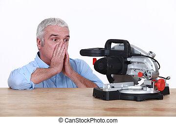 Mature looking at his circular saw with disarray