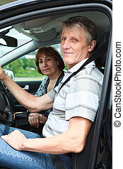 Mature male and woman sitting in land vehicle and smiling