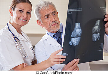 Mature male doctor and young female assistant analyzing patient