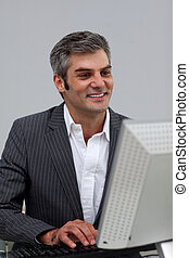 Mature male executive working at a computer