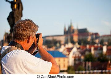 mature male photographer photographs morning Prague