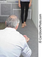 mature male podologist examining female patient walking