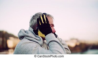 Mature male runner putting on headphones outdoors in city. -...