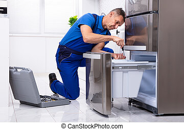 Serviceman Repairing Refrigerator - Mature Male Serviceman ...